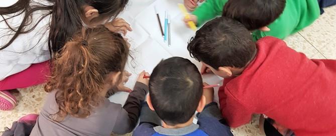 ילדים מציירים במשותף על נייר גדול