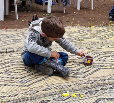 ילד מקשט את העציץ שיצר